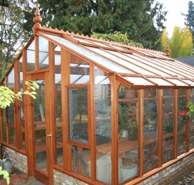 Tall redwood and glass greenhouse with Jalousie windows