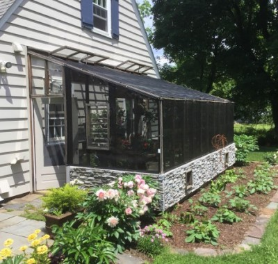 Exterior of 10x18 Lean-to greenhouse with  two 2x8 redwood beams used as a patio space