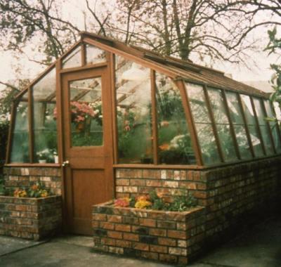 Glass greenhouse with brick base wall