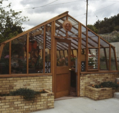 Large home greenhouse on brick base wall