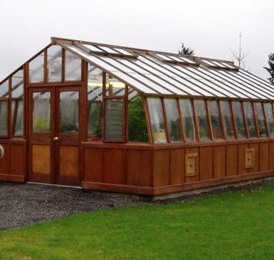 Large home redwood greenhouse with double doors