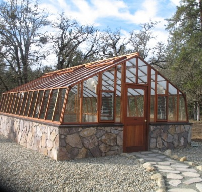 Large home greenhouse on stone base with Jalousie windows
