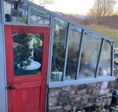 Door end view of 9x12 Tropic Lean-to greenhouse with stone base wall and Dutch door