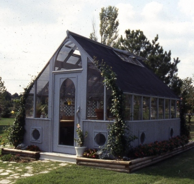Redwood greenhouse stained gray with wood base and shade cloth