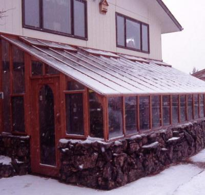 Redwood lean-to greenhouse with stone base